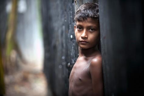 En pojke utanför sitt hem i slummorådet Karial i Bangladesh. Sipa Press/Kibae Park