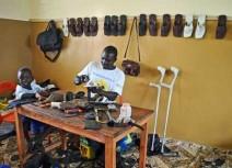 Umaru Kargbo, som blev förlamad i benen 10-åring, kan tack vare sin yrkesutbildning nu försörja både sig själv och sin familj. Här i sin verkstad tillsammans med sonen Mohammed.