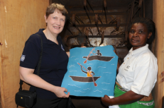 Helen Clark with one of the eight women working in a batik factory in Mtandire, Malawi. UNDP supports a women's economic empowerment project which provides vocational training and the tools needed to start the batik producing center. (Photo: UNDP/Helen During)