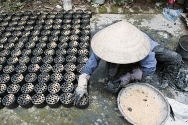 En kvinna i byn Ba Trang, i Vietnam, gör biomassabriketter som bland annat används för matlagning. Biomassan är tillverkad av jordbruksavfall och används ofta som ersättning för kol. Foto: UN/Photo, Kibae Park.